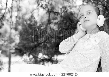 Pretty Little Girl Listening And Enjoying Music Using Headphones At Summer Day
