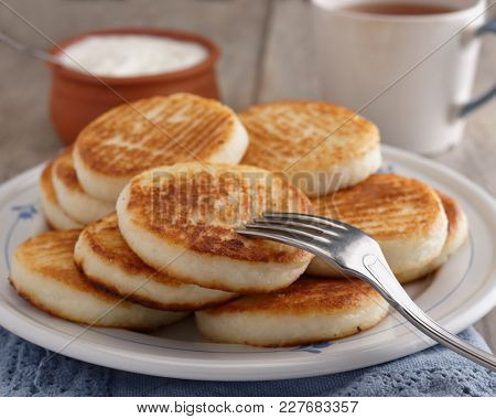 Syrniki, the traditional Russian cheese pancakes on a rustic table