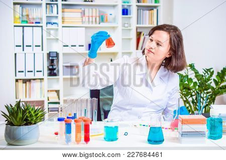 Girl Scientist Holding Laboratory Flask In Hand. Researcher Researching In The Laboratory. Reagent F