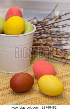 Easter Eggs In A Bed Of Straw In A White Bucket, Three Other Eggs In Front Of A Bucket In The Backgr