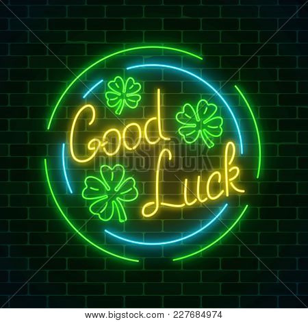 Glowing Neon Sign With Geed Luck Wish And Four-leaf Clovers In Circle Frames On Dark Brick Wall Back
