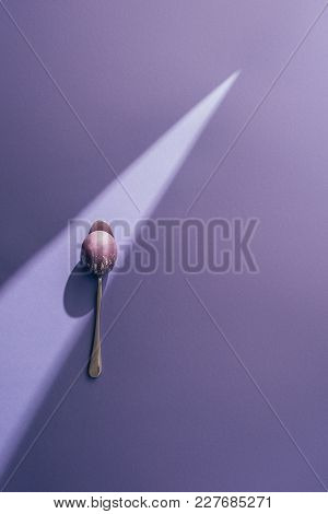 Easter Painted Egg In Spoon On Purple Background With Sunbeam