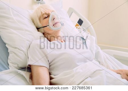 Recovery Process. Senior Lady Sleeping Gin A Hospital Bed And Wearing A Respiratory Support Mask Whi