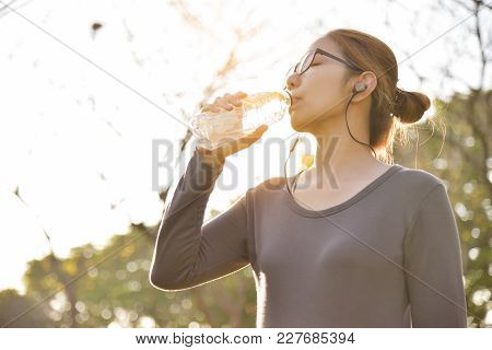 Young Asian Female  In Grey Sportswear Is Resting And Drinking Water While Exercise At Park. Woman L