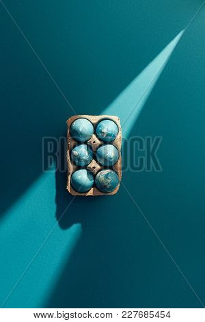 Top View Of Blue Easter Eggs In Tray, On Blue With Sunbeam
