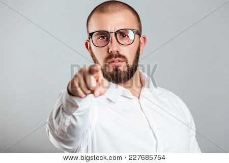 Photo closeup of determined guy in white shirt and glasses pointing on camera index finger with prosecution isolated over gray background
