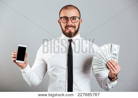 Photo of successful man 30s in glasses and tie holding cell phone and fan of dollar bills isolated over gray background