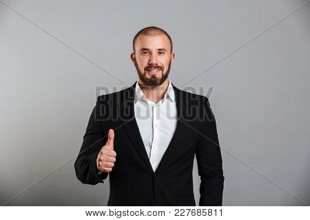 Portrait of pleased masculine man in business suit posing on camera with thumb up isolated over gray background