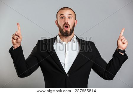 Image of surprised caucasian man in black business suit posing on camera and pointing fingers upward on copy space isolated over gray background