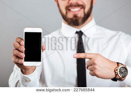 Close up of a smiling businessman pointing finger at blank screen mobile phone isolated over gray background