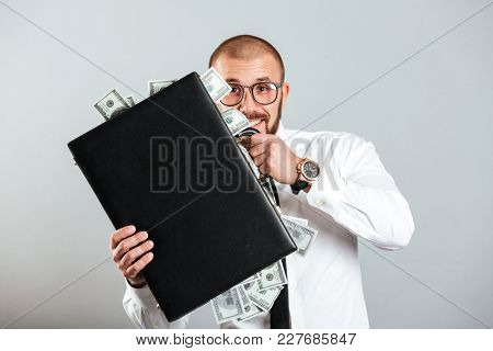 Happy business man in glasses and shirt holding diplomat full of cash money isolated over gray background
