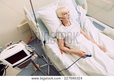 Feeling Better. Top View On A Senior Lady Looking Into Vacancy While Lying In A Hospital Bed With An