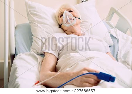 Staying In A Good Mood. Positive Minded Senior Lady Smiling While Lying In A Hospital Bed With An Ox