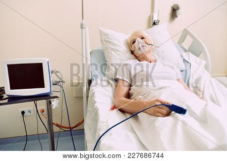 Feeling Better Today. Elderly Woman Undergoing Treatment And Staying In A Hospital With A Pulse Oxim