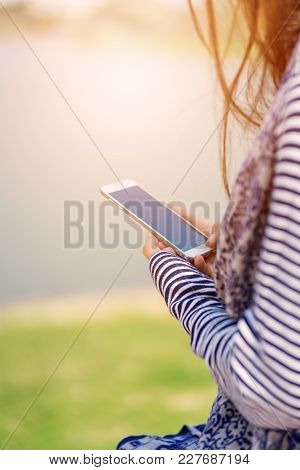 Hand Holding Smartphone With Blur Nature Background.