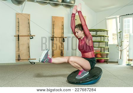 Young Beautiful And Attractive Fitness Girl Workout On Her Balance By Standing On The Half Ball On T