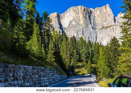 Road in the Dolomite Alps. Majestic white mountains and rocks. The beautiful sunny day. The concept of active, extreme and automobile tourism