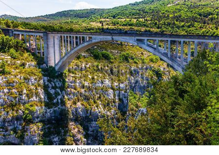 Grandiose bridge over the mountain canyon Verdon, Southern France, Provence. The picturesque deep Verdon Gorge in the Mercantour Park. The concept of active and extreme tourism