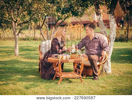 Happy Couple Sitting At The Table And Drinking Tea Outdoors