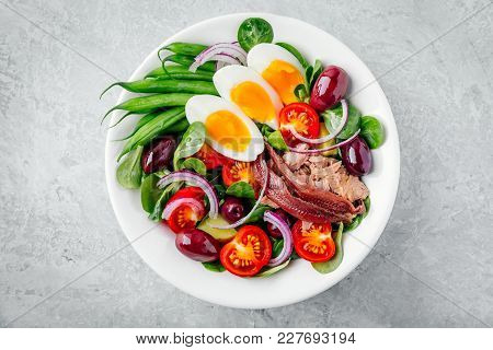 Nicoise Salad With Tuna, Anchovies, Eggs, Green Beans, Olives, Tomatoes, Red Onions And Salad Leaves