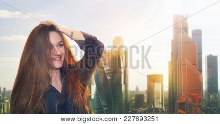 Smiling Red-haired Girl On The Background Of Skyscrapers Of Moscow City. City Panorama. The Backligh