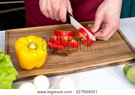 Hand Slice Red Pepper With Ceramic Knife On Wooden Cutting Board. Vegetarian, Health, Diet Concept.