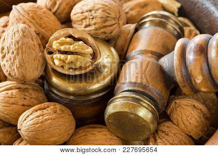 Opened Walnuts in vintage wooden nut bowl with brass Nutcracker gavel hammer