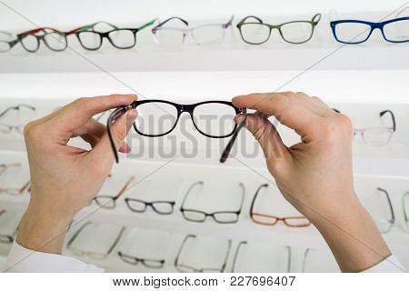 Male Hands Holding Glasses At Optical Store, Out Of Focus Showcase With Many Glasses.