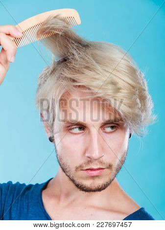 Hairdo Coiffure Hairstyle Concept. Handsome Young Fashion Model Combing His Colored Blonde Hair Usin