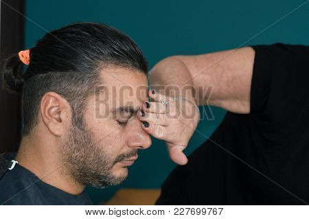 Female Barber Cleaning Young Man's Face With Her Hand After Shaving His Hair