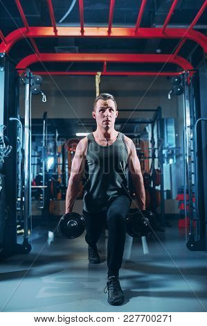 Young Muscled Man Working Out With Dumbbells In Gym