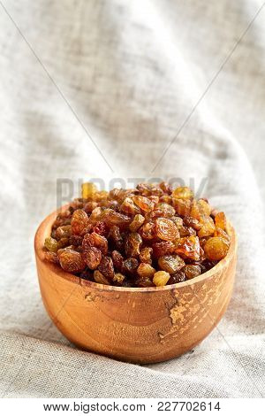 Close-up Picture Of Wooden Bowl With Golden Raisins On Light Grey Tablecloth Or Napkin, Copy Space,