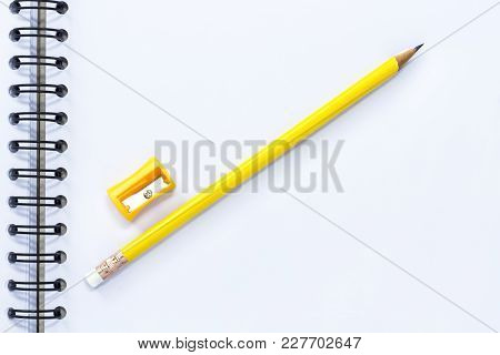 Pencil-sharpener And Pencil Isolated On Notebook Background.  With Copy Space For Your Text.