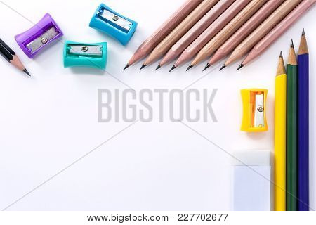 Many Pencil-sharpener, Eraser, And Many Pencils Isolated On White Paper Background. With Copy Space