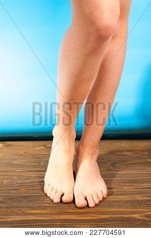 Young Girl Steppe Feet With Itchy Feet Uses His Big Toe To Scratch His Other Foot On Wooden Floor