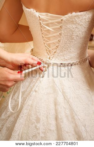 Wedding Day. Morning Of The Bride. Fees. Dressing. Hands Tighten The Wedding Dress. Close Up
