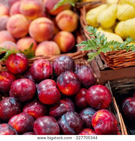 Red Ripe  Organic Plums In The Market.  Whole Fresh Plums Harvest.  Food Background