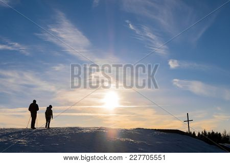 Father And Son Hiking On Snowy Mountain Schoeckl To Summit Cross With Nice Sunset In Austria