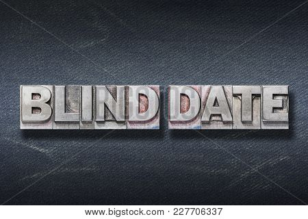 Blind Date Phrase Made From Metallic Letterpress On Dark Jeans Background