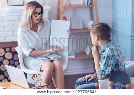 What Can You Say About This. Adult Therapist Wearing Glasses Holding A Piece Of Paper While Testing