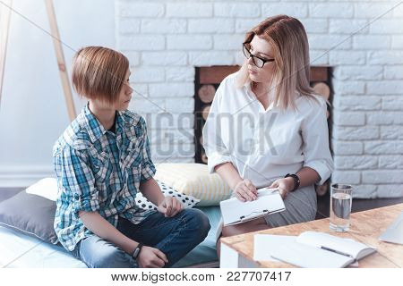 Tell Me About Your Fears. Female Therapist Holding A Clipboard And Sitting Next To A Male Kid While