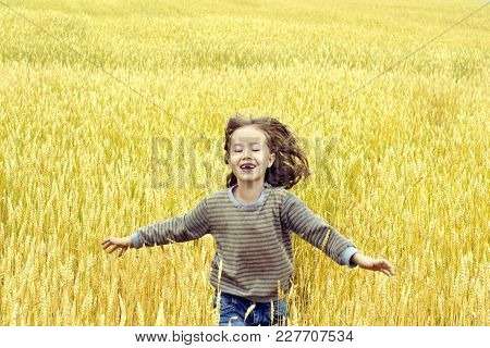 Happy Children On The Background Of Yellow Wheat Fields