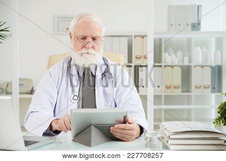 Senior General Practitioner Reading Information On Digital Tablet