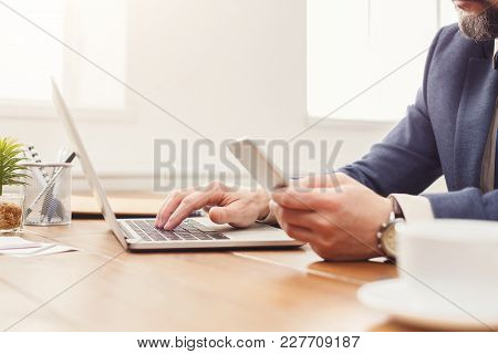 Unrecognizable Businessman With Mobile App And Laptop In Modern Office, Working On Computer And Smar
