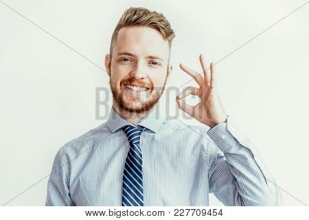 Closeup Portrait Of Smiling Young Attractive Business Man Looking At Camera And Showing Ok Sign. Iso
