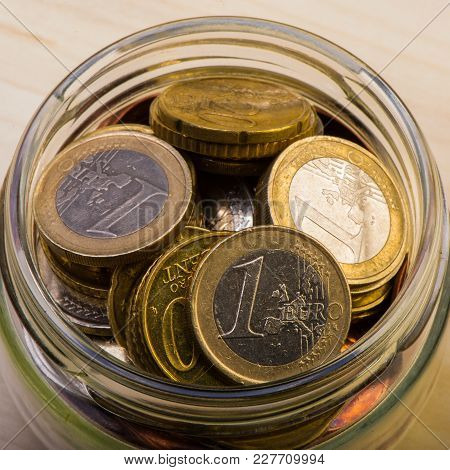 Group Of Coins One Euro In A Glass Jar. Euro Money.  Currency Of The European Union.