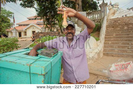 Dikwella, Sri Lanka - Dec 30, 2017: Seller Of Ice Cream On The Street Demonstrating The Quality Of D