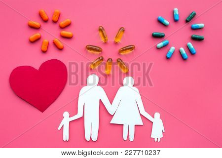 Prevention Of Diseases. Medicine For Family Health. Color Pills Near Silhouette Of Family On Pink Ba