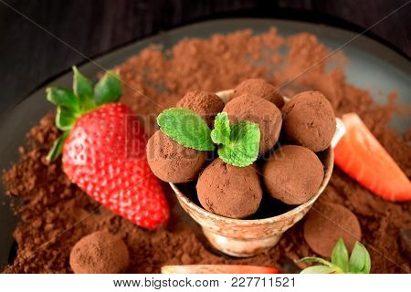 Chocolate Truffles Covered With Cacao Powder In A Brown Cup Surrounded By Strawberries