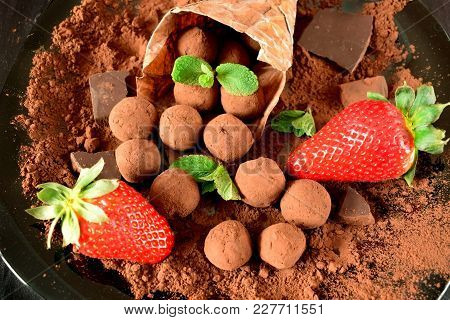 Chocolate Truffles Covered With Cacao Powder And Strawberries Are Falling Out Of The Paper Package